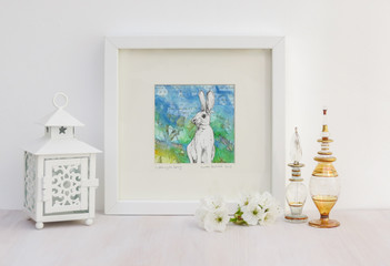 White interior display. Drawing of rabbit with ears pricked on a collaged summery blue and green background in frame. With egyptian glass scent bottles, tea light and cherry blossom.