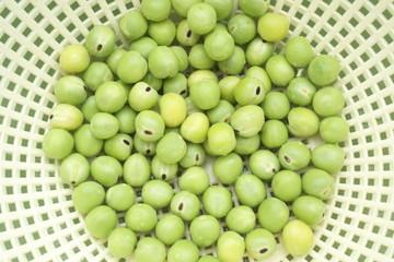 新鮮なグリーンピースと水切りかご - Fresh green peas in a drainer