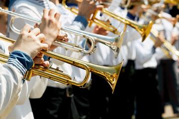 Closeup of children's brass band. Children play on golden pipes.