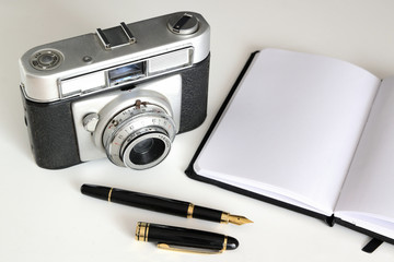 Vintage camera, pen and notebook for the nostalgic journalist and graphic reporter. Empty copy space for Editor's text.