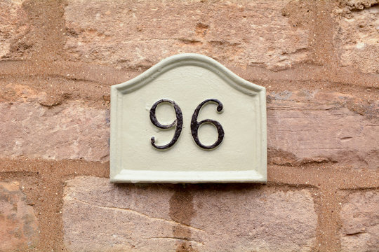 House number 96 sign fixed to wall