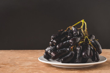 Black seedless moon drops grape or Witch fingers grape in white plate with black background. copy space