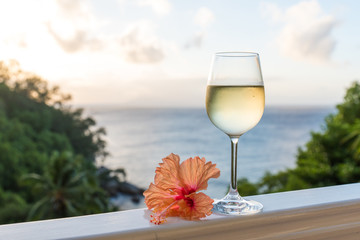 Romantic moments in summer at sunset with two glasses of white wine - Relaxing romantic holiday concept with beautiful view of tropical beach and coast