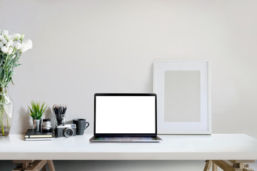 Stylish creative workspace with laptop computer and mockup poster on home or studio.