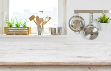 Copy space on wooden table top over blurred kitchen interior
