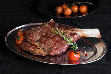 Single tomahawk rib steak on silver dish next to roasted cherry tomatoes