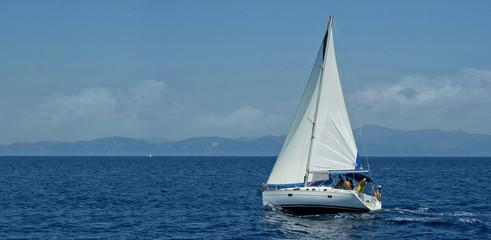 White sailboat traveling the sea