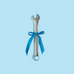 a wrench with a blue gift ribbon on a blue background. A concept for Father's Day. Best gift.