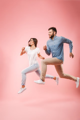 Full length portrait of a funny young couple running fast
