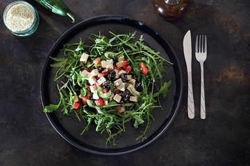 Foto op Aluminium Voorgerecht Zdrowa sałatka. Zielona sałatka na rukoli, z arbuza, tofu, czarnych oliwek podana na czarnymi talerzu