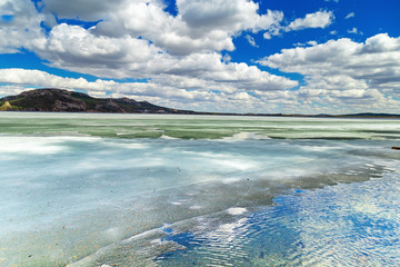 Picturesque landscape in Burabay National Nature Park, Kazakhstan. Shore of big Lake Borovoe (Burabay) in ice. Clouds are reflected in a frozen lake. May 2018.