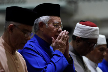 Malaysia's Prime Minister Najib Razak (C) offers special prayers a day before the 14th general election at a mosque in Pekan, Pahang