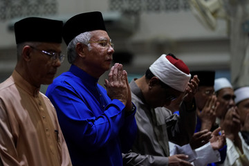 Malaysia's Prime Minister Najib Razak (2nd-L) offers special prayers a day before the 14th general election at a mosque in Pekan, Pahang