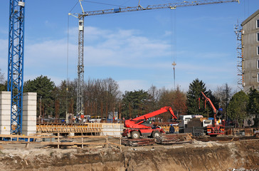new building construction site with cranes and workers