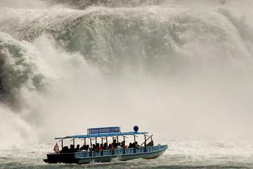A tourist vessel sails past the Rhine Falls in Neuhausen