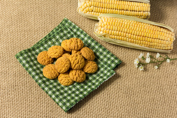 Delicious yellow cookie of corn. Sweet food of Festa Junina, a typical brazilian party. Snack on plaid fabric and jute.