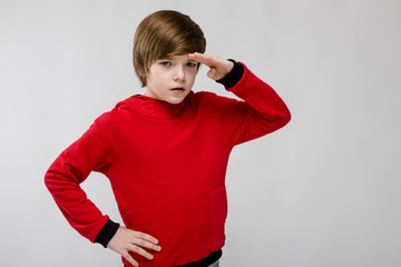 Cute confident caucasian little boy in red sweater looking into distance on grey background