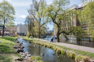 Unrecognizable people enjoy waterfront park Strömparken along Motala river in Norrkoping during spring in Sweden.
