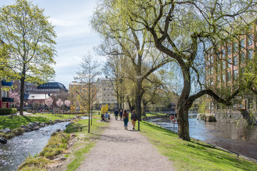 Unrecognizable people enjoy waterfront park Strömparken along Motala river in Norrkoping during spring in Sweden.