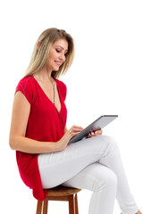 Happy woman watches digital tablet videos. Blonde person and wearing red clothes. Isolated.