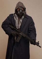 Man with hood, rifle and gas mask.