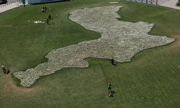 Workers mow lawns next to the shape of the Korean peninsula which was made in the wish for the success of the summit between North and South Korea which was held last month,  in front of City Hall in Seoul