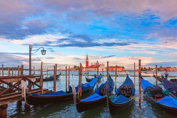 Gondolas moored by Saint Mark square with Church of San Giorgio Maggiore in the background at sunset, Venice, Italia