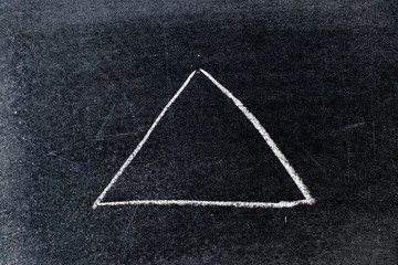 White chalk drawing in triangle shape on black board background