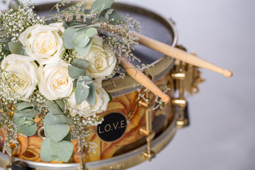 "The white rose drumsticks is placed on a snare drum. There are nobody. There is text ""LOVE"" on black circle space beside the drum."