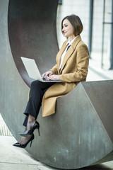 manager con cappotto beige, lavora al computer in una piazza.