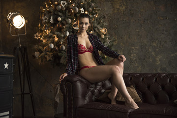 Beautiful girl in red linen on the couch near Christmas tree