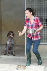 dedicated girl training dog in kennel