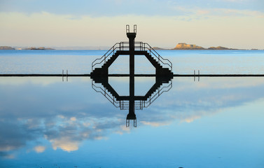 Diving board reflection on sea water swimming pool in Saint Malo, France