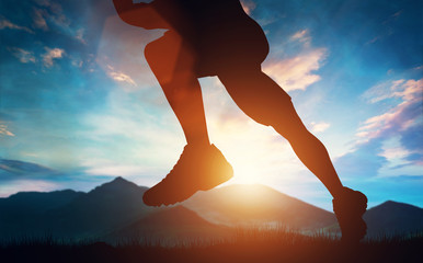Man running in the mountains at the sunset.