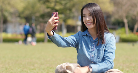 Woman taking selfie on mobile phone in city park
