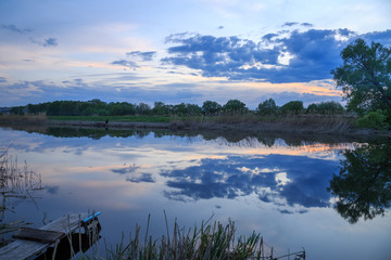 A serene evening at sunset by the river, an excellent place for Russian fishing. The sky was covered with dark clouds.