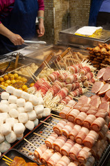 Mid section of a man preparing food at a night market stall