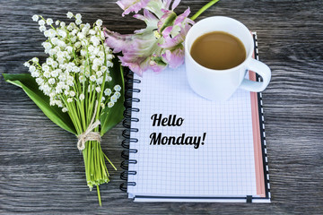 Notebook,Bouquet of Lily of the Valley ,Tulip and Cup of Coffee .Spring Morning Concept with Hello Monday Message