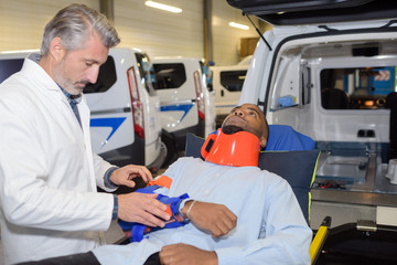 Man with neck brace at open doors of ambulance