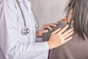 female doctor examining a patient suffering from neck and shoulder pain