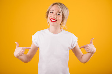 Cool blonde woman in white t-shirt. Yellow background