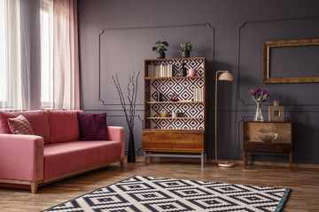Retro wooden cupboard with books and decor standing in dark room interior with pink sofa, carpet and flowers in glass vase