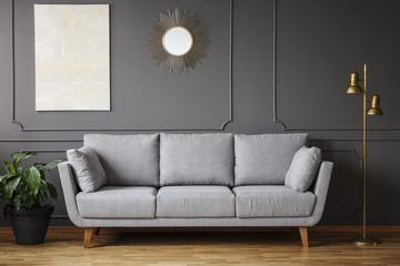 Decorative mirror and modern art painting hanging on the wall with molding in dark grey living room interior with fresh plant, gold lamp and bright sofa