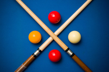 Balls and a cue seen on the table of a Carom Billiard