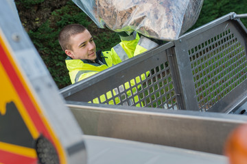 young dustman putting collected leaves in lorry