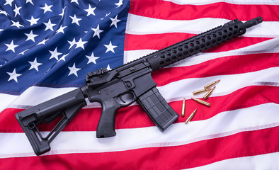 Custom built AR-15 carbine and bullets on American flag surface, background. Studio shot.