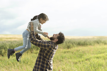 father lifting daughter in spring image