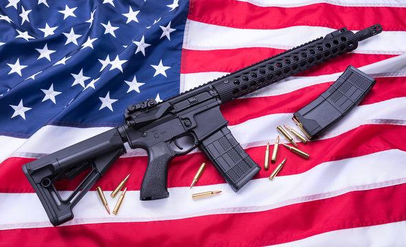 Custom built AR-15 carbine, bullets and a magazine on American flag surface, background. Studio shot.