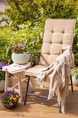 garden chair on terrace in sunlight, pansy flowers