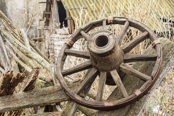 Old wooden wheel on background of ruins of old farm. Copy space